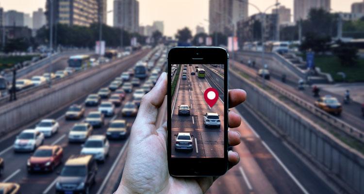 trojprúdová diaľnica s autami a v popredí ruka s mobilom a mobilnou aplikáciou
